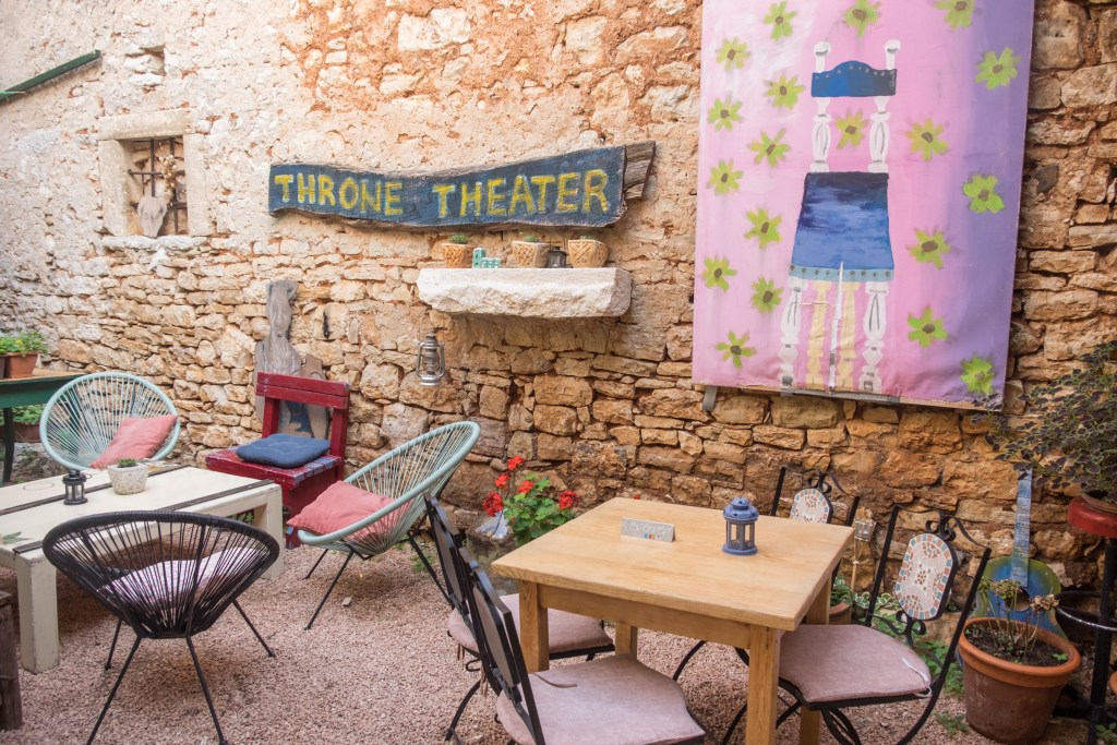 """A courtyard cafe. You see wooden tables with different unmatched chairs, a wooden painted sign that reads """"Throne Theater"""", shelves with small flowerpots on them, and a painting of a chair with flowers on the background."""
