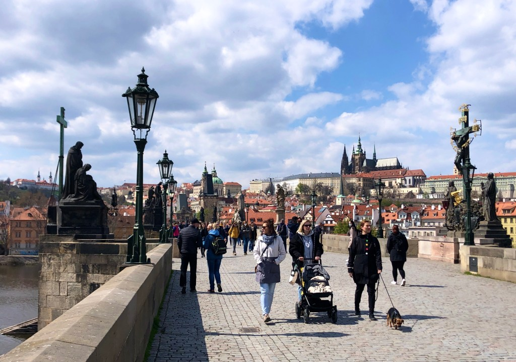 The stone Charles Bridge in Prague, lined with statues on each side and Jesus on a cross on the right. A few dozen people are walking on it, including three women with a stroller and a small brown dog. In the background you see Prague Castle and lots of buildings with orange roofs.