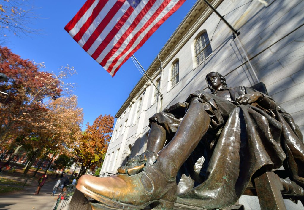 The John Harvard statue, a statue of a man sitting in a chair. It is brown but his foot has been rubbed a lot so it's turned gold. An American flag and autumn leaves on trees in the background.