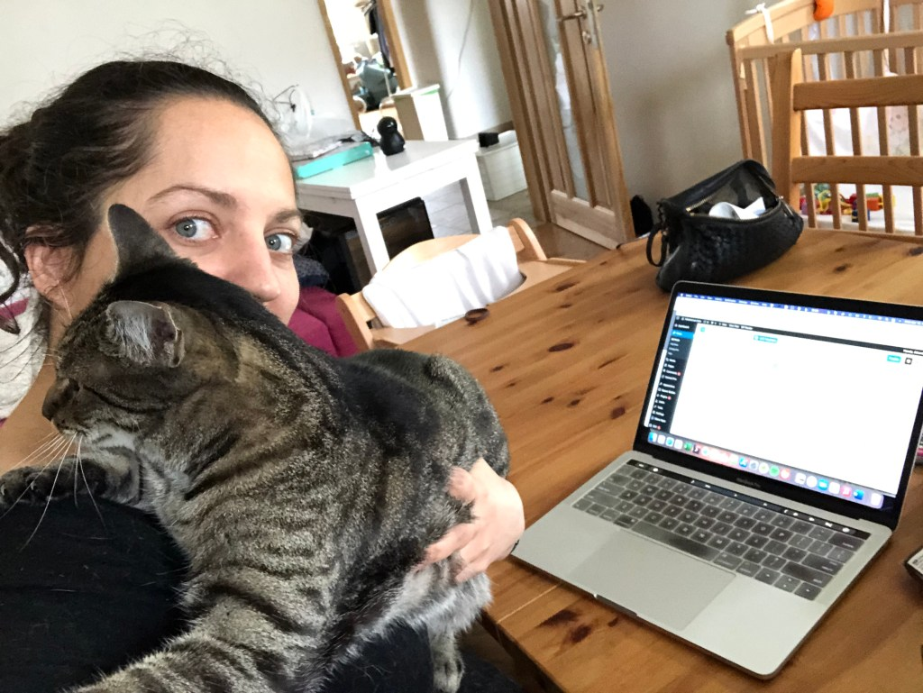 Kate tries to work on her laptop at the table but Baliček keeps insisting on climbing her, his paws on her shoulders and his head mashed up next to hers.