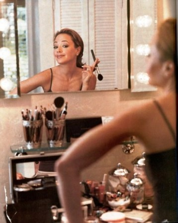 woman applying makeup in a mirror