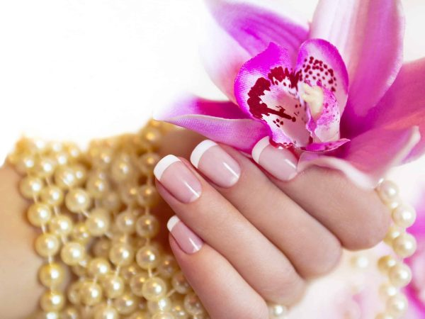 17010639 – french manicure to a woman s hand with an orchid and beads