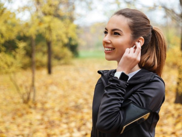 Portrait of a smiling fitness girl listening to music outdoors