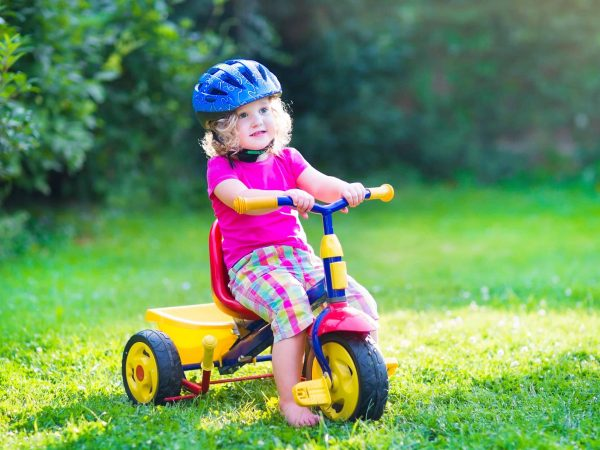 Cute funny toddler girl riding her bike wearing a safety helmet enjoying a nice sunny day in a summer garden playing outdoors
