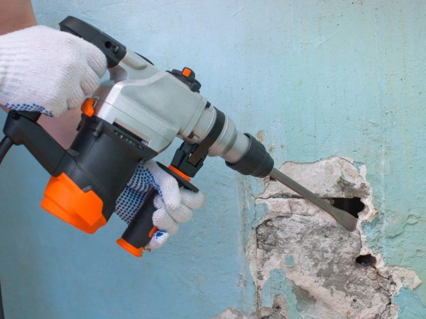 The builder with hammer drill perforator equipment making hole in wall at construction site.