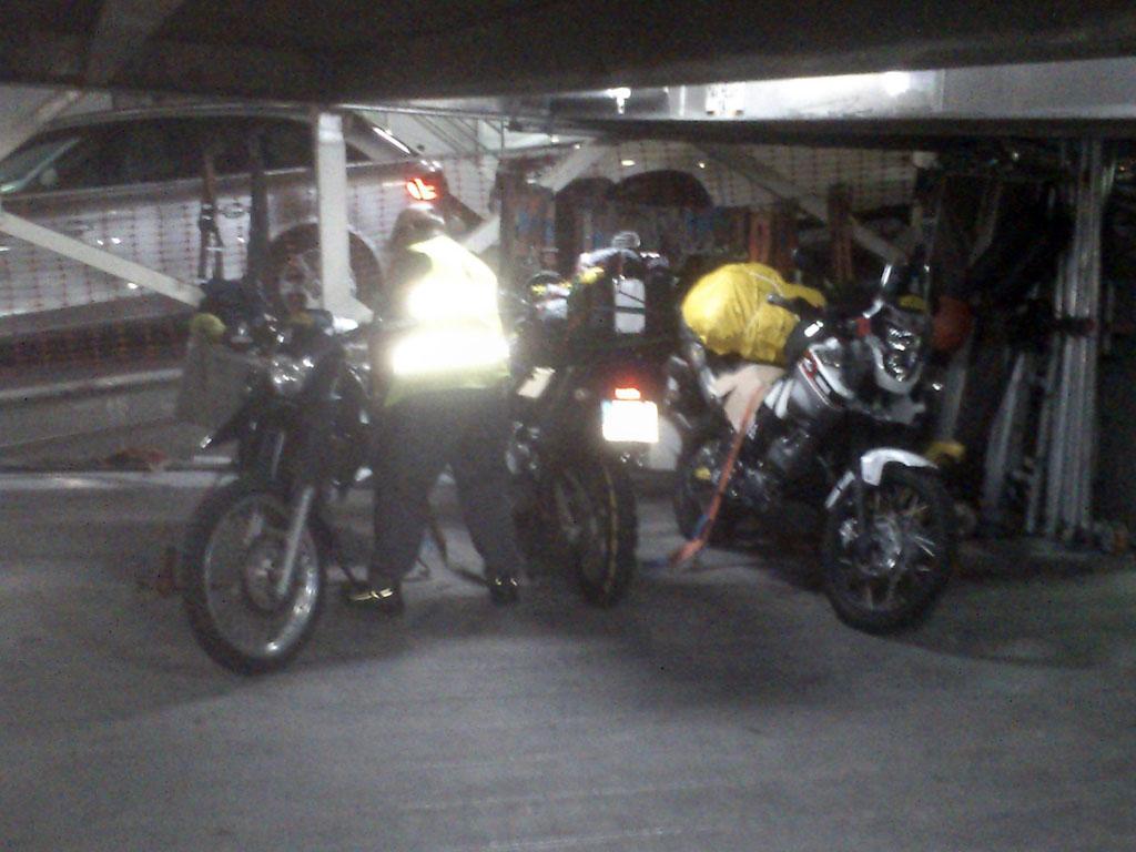 Peón atando las motos en el ferry.