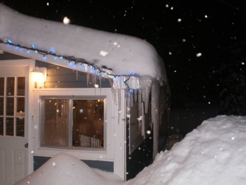 Christmas lights and mountains of snow reaching porch windows.