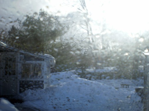 Snow, part of a house, trees & more snow through a rain splotched windshield.