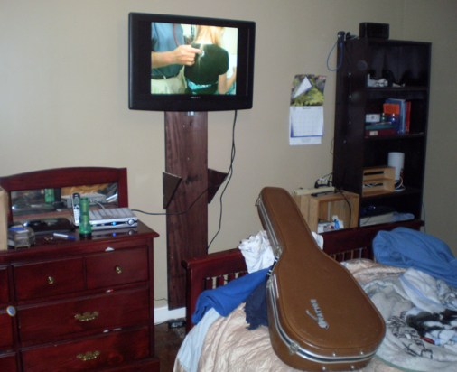 Flat panel teevee on a wall with a stained piece of wood to help hold it in place.