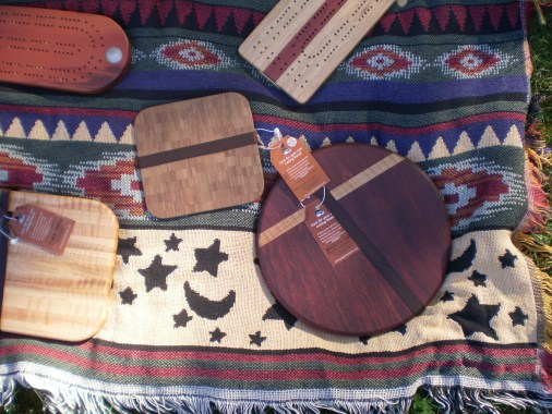 Corner of a blanket with Some handmade breadboards and cribbage boards.