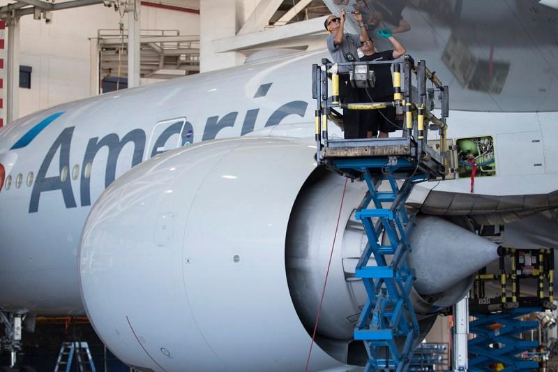 Mecânicos da American Airlines trabalham na asa de um Boeing 777
