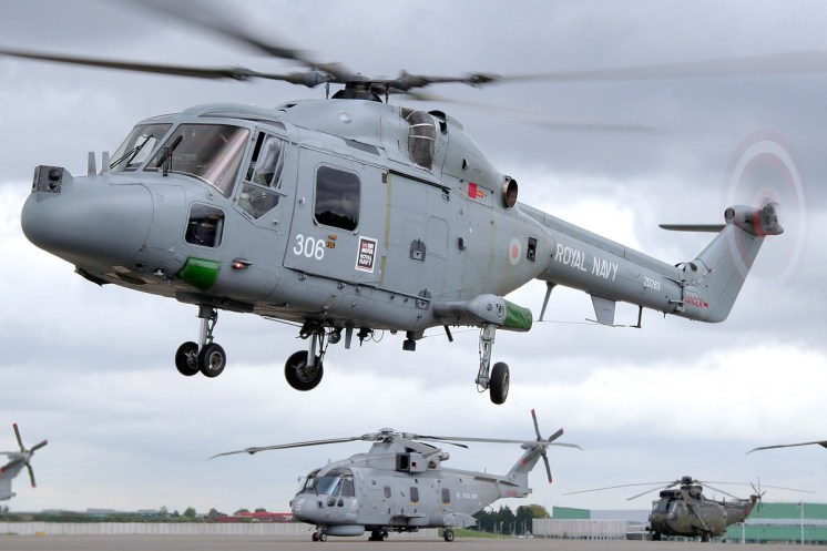 © Mark Kwiatkowski - Lynx HMA8 in the hover with a Merlin in the background - Royal Navy Lynx Retirement