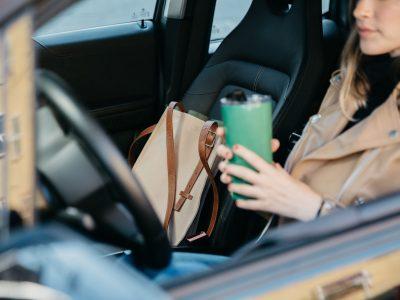 Camel Aerrem bag in passenger seat, driver parked holding green reusable tumbler