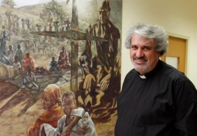 """Jesuit Father Peter Balleis, outgoing international director of Jesuit Refugee Service, is pictured at the service's office at Jesuit headquarters in Rome Sept. 7. Father Balleis said a photograph, such as the recent one of the 3-year-old Syrian boy who drowned, """"can evoke compassion and rethinking."""" The background image shows Father Pedro Arrupe, former Jesuit Superior General, and refugees. (CNS photo/Paul Haring) See JRS-REFUGEES-IMAGES Sept. 8, 2015."""