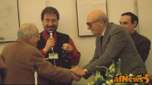 La storica stretta di mano fra Giovabattista Carpi e Will Eisner - dietro Gianfranco Goria e Luca Boschi - Foto GGoria