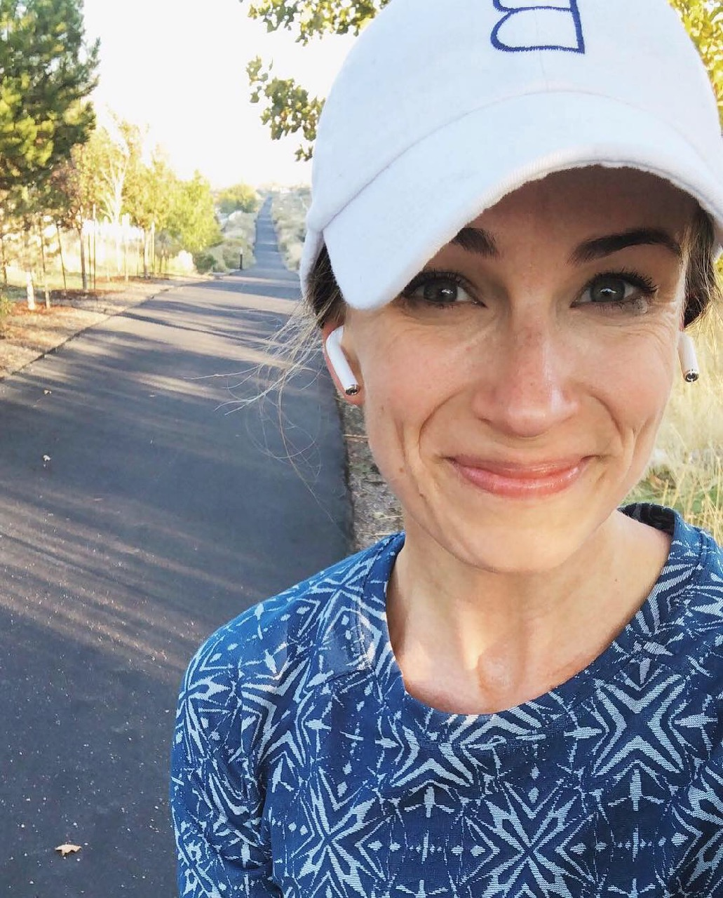 runner with airpods listening to the best running music