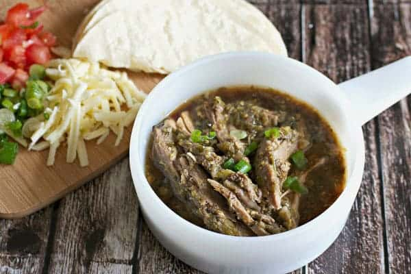 Add a boneless pork butt in the slow cooker, top it with a large can of puréed tomatillos, fresh chopped cilantro and some spices, and then cook it on low for 8 hours. Result: YUM!