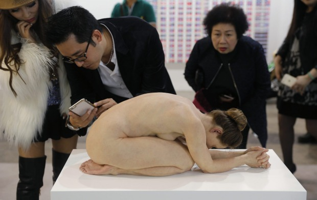 Visitors take photos of the hyper-realist sculpture 'Untitled (Kneeling Woman)' created by Australian artist Sam Jinks during the VIP preview of the Art Basel art fair in Hong Kong on Friday, March 13, 2015. Art Basel stages modern and contemporary art shows and is held annually in Basel, Switzerland, Miami Beach and Hong Kong.