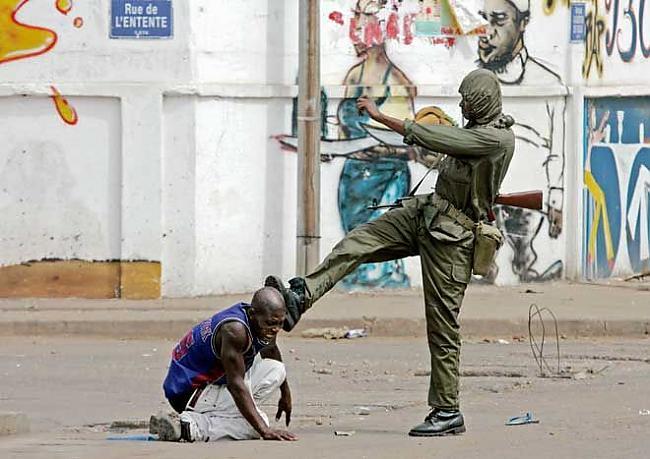 soldato calcia dimostrante