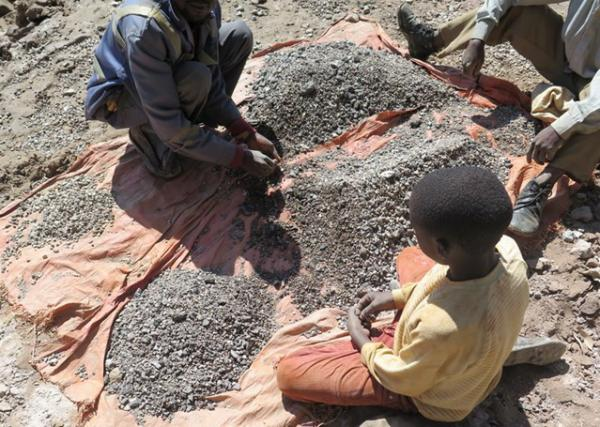 Charles, 13 years old, works with his father in the afternoons and goes to school in the morning when he has the money. Charles sorts and washes the minerals, before helping to transport them to a nearby trading house, which buys the ore, May 2015. © Amnesty International and Afrewatch