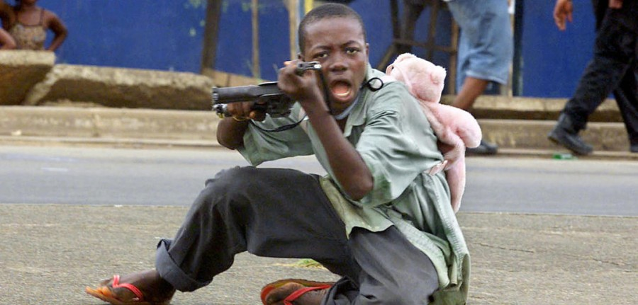 "Monrovia, LIBERIA: (FILES) A child soldier wearing a teddy bear backpack points his gun at a photographer in a street of Monrovia 27 June 2003 where Liberian President Charles Taylor's forces took control of the city. At the iniatitve of French Foreign Minister Philippe Douste-Blazy, France will host 05 and 06 February 2007 in Paris an international conference on children involved in armed forces and armed groups called ""Let US Free the Children of War"". Co-presided by Philippe Douste-Blazy and Ann M. Veneman, executive director of UNICEF, and in the presence of Radhika Coomaraswamy, the UN secretary-general?s special representative for children in armed conflict, the conference will bring together representatives of nearly 60 countries, including many ministers, the European Union, many international organizations, including the United Nations, and representatives of civil society, in particular former child soldiers and NGO leaders active on the ground. AFP PHOTO FILES GEORGES GOBET (Photo credit should read GEORGES GOBET/AFP/Getty Images)"