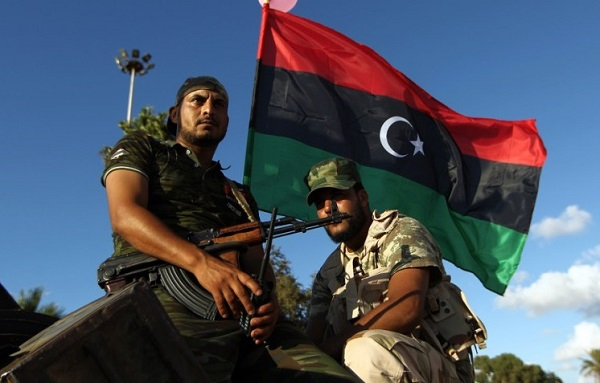 """Libyan troops loyal to Khalifa Haftar, a retired general and former chief of staff for Moamer Kadhafi, sit on an amoured personnel carrier (APC) during a demonstration calling on the international community to arm the Libyan army on August 14, 2015 in the eastern Libyan city of Benghazi. The Tobruk-based government (recognised by the international community) said in a statement that world powers were using """"double standards"""" by fighting IS in Syria and Iraq and """"turning a blind eye"""" to the presence of the jihadists in Libya. AFP PHOTO / ABDULLAH DOMA"""