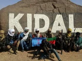 Miliziani tuareg in posa sotto il masso con la scritta Kidal, posizionato all'ingresso della città