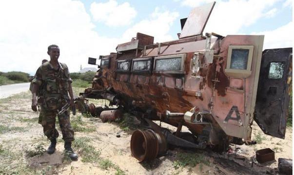 Un soldato somalo passa accanto a un veicolo militare dell'AMISOM (African Union Mission in Somalia), ne distretto di Daynile, alla periferia di Mogadiscio (foto REUTERS/Feisal Omar)