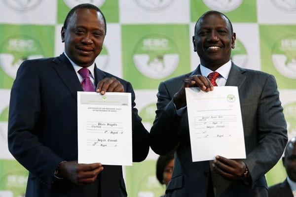 Uhuru Kenyatta e il suo vice William Ruto mostrano i certificati che li confermano nelle rispettive cariche