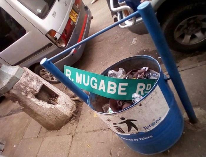 La targa della strada che porta il nome di Mugabe buttata nella spazzatura