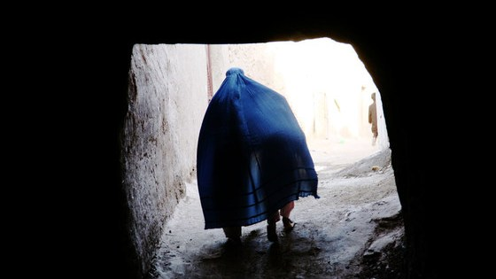 An Afghan woman covers a child under her Borqa while passing through a tunnel in Herat, Afghanistan.