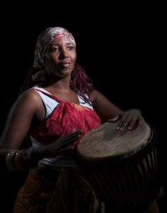 freeimage-19931797-web-An african drummer plays a djembe drum set against a dark background