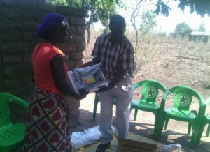 The GILEP Director hands over a sewing machine to Rose Patrick, Village Headwoman Namate.