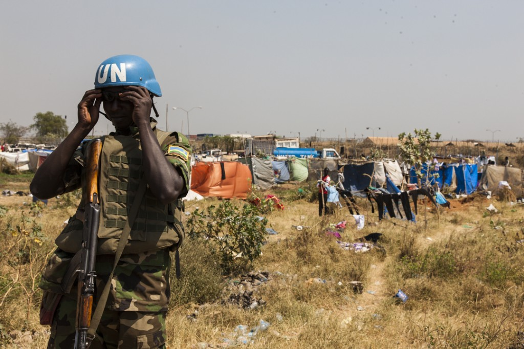 A Rwandan UN peacekeeper puts on his sunglasses while standing guard outside of the IDP camp in the UNMISS compound that now contains more than 25,000 people of the Nuer tribe who are seeking refuge in Tong Ping, Juba, South Sudan, January 17, 2014.