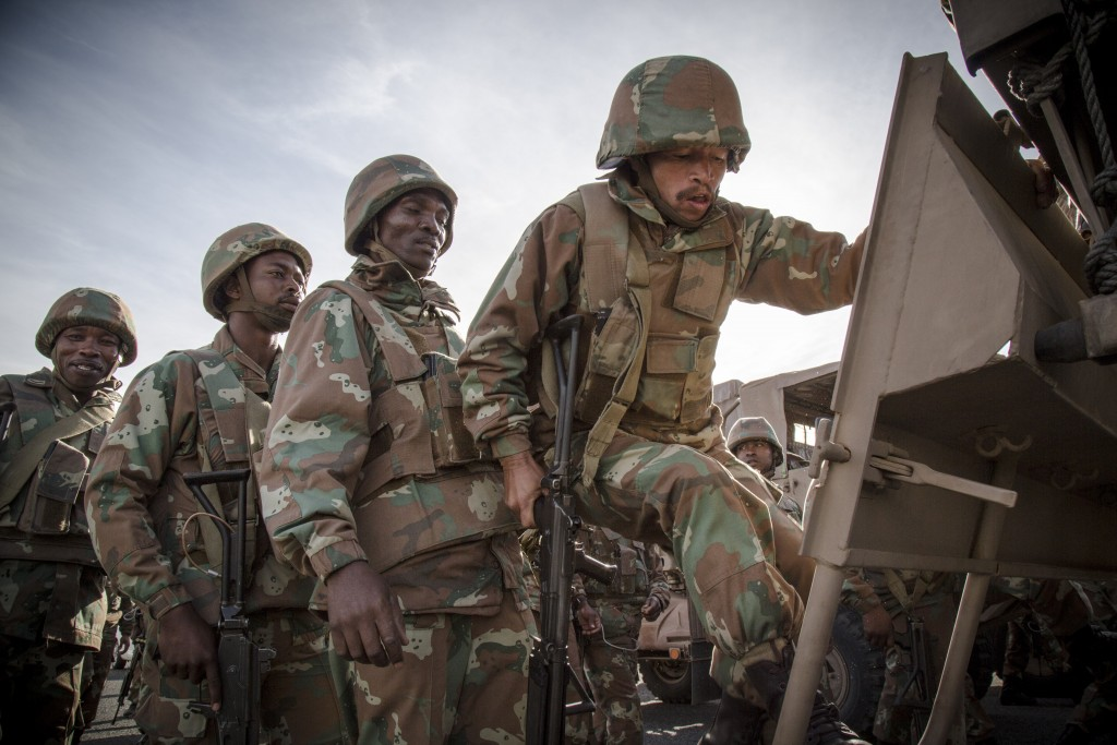 SANDF soldiers board a SAMIL truck while on operations in South Africa - Photo by Trent Perkins
