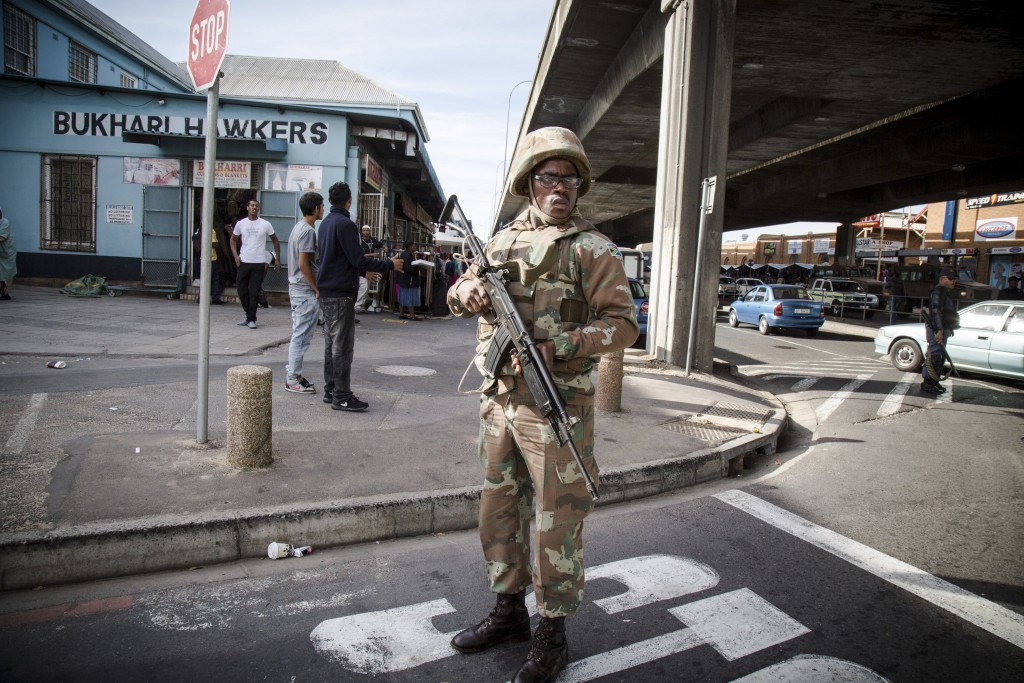 An SANDF soldiers stands guard at the perimeter of a police-led cordon and search operation. The soldiers are not permitted to carry out standard law-enforcement actions, so they did not take direct part in the searches and arrests. TRENT PERKINS/ADR