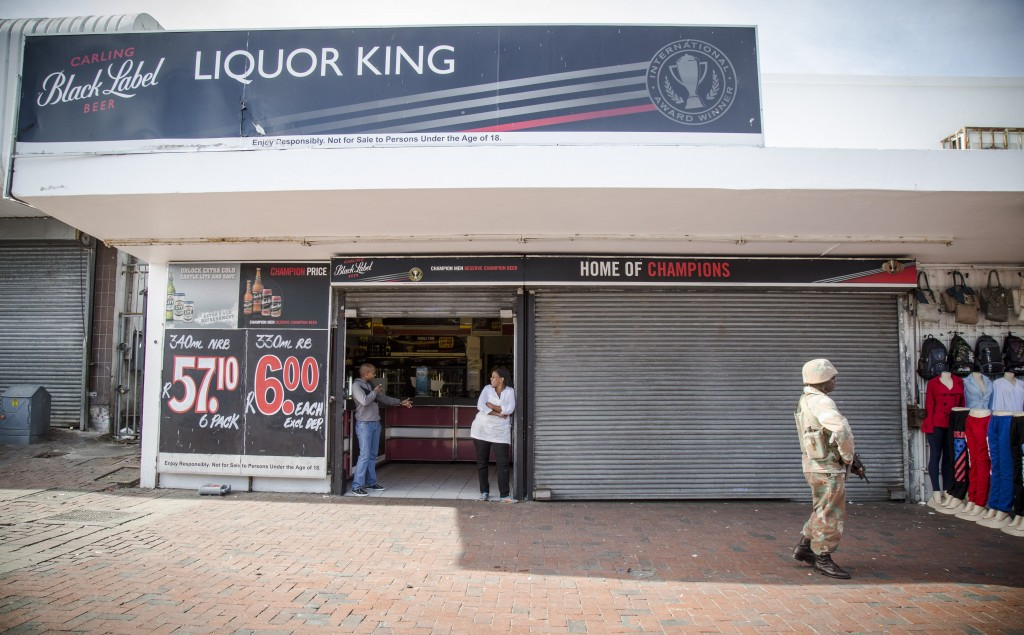 Store owners and staff watch as SANDF soldiers walk past during a police-led cordon and search operation in Bellville, Western Cape. TRENT PERKINS/ADR