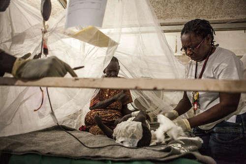 L'équipe medica di MSF cerca di abbassare la temperatura di questo giovane paziente affetto da malaria, in attesa di poter operare una trasfusione di sangue. Il ragazzo aveva 39,8° di febbre e attraverso l'applicazione di cotone bagnato, gli operatori sono riusciti ad abbassarla di quasi 2 gradi. Foto di Brendan Bannon. POC di Bentiu, Sud Sudan. Settembre 2015.