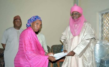 Representative of Sarkin Shanun Kano, Alhaji Mustapha Hashim presenting a letter of award to Amina Ladan of LADACO Group