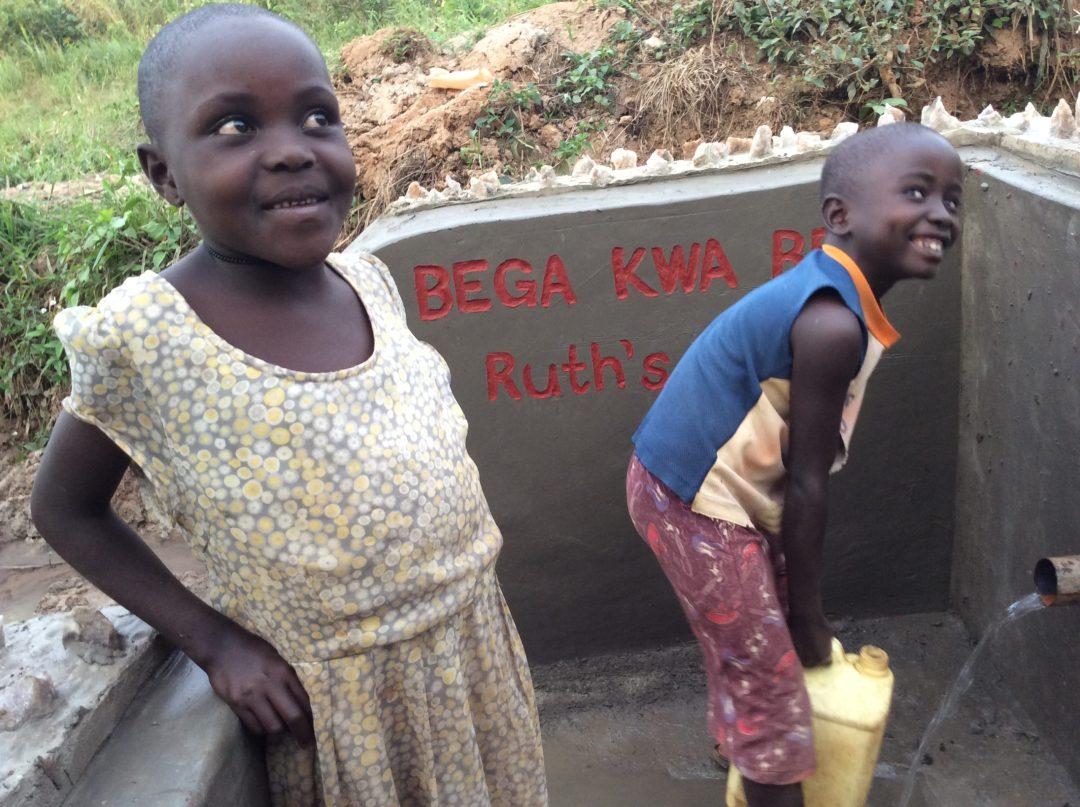 Children in Uganda get safe drinking water from a well