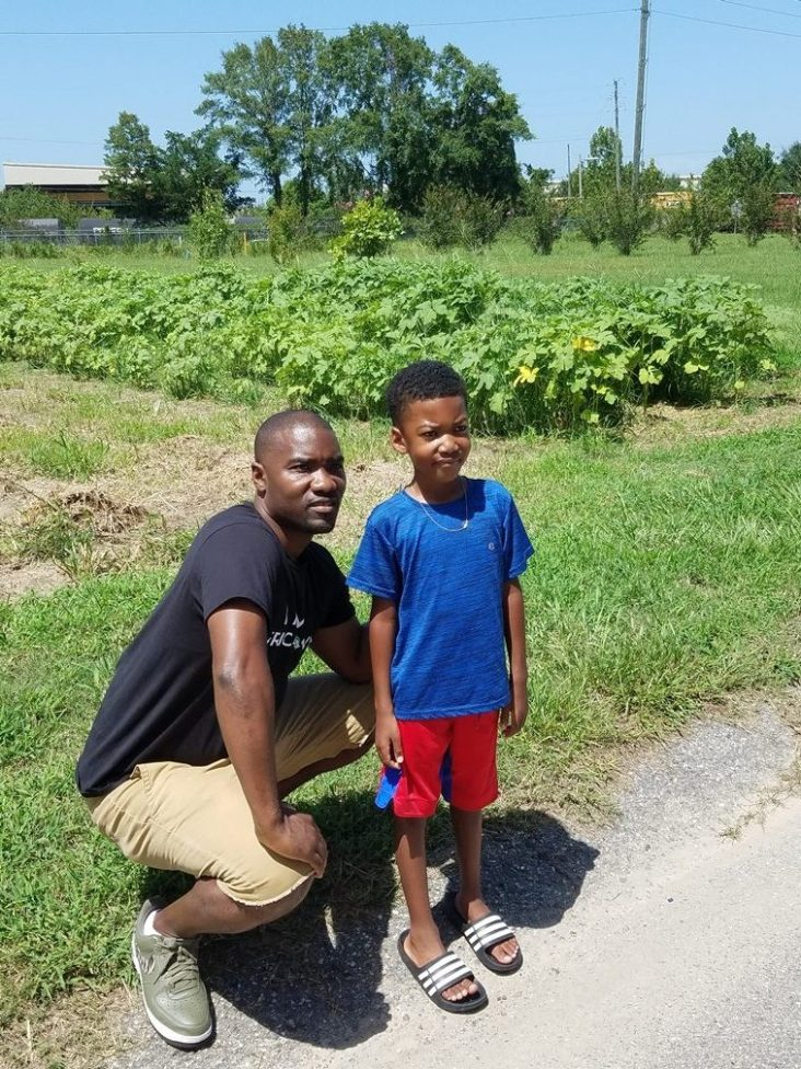 Garrett and his son pose next to Africatown's large community garden.