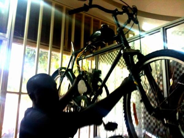 Julius sosteniendo un bicicleta motorizada Adtec en su tienda de Nairobi