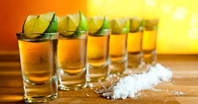 Tequila, lime and salt on wooden table