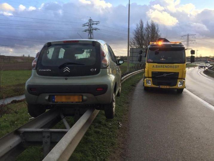 Oops! Motorist 'parks' perfectly on the barrier of highway