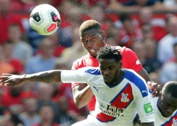 Manchester United's French midfielder Paul Pogba (top) wins a header from Crystal Palace's German midfielder Jeffrey Schlupp (C) during the English Premier League football match between Manchester United and Crystal Palace at Old Trafford in Manchester, north west England, on August 24, 2019. (Photo by Lindsey Parnaby / AFP)