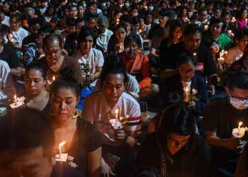 """People take part in a candle light vigil for victims following a mass shooting in Nakhon Ratchasima on February 9, 2020. – A Thai soldier who killed at least 26 people before being shot dead in a mall by commandos went on the rampage because of a debt dispute, the kingdom's premier said on February 9, offering the first official speculation for the motive of an """"unprecedented"""" shooting spree. (Photo by CHALINEE THIRASUPA / AFP)"""