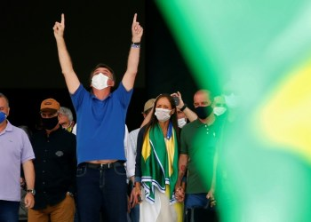 """Brazilian President Jair Bolsonaro (C) compares the coronavirus to a """"little flu,"""" condemns the """"hysteria"""" surrounding it and is urging the country to get back to work to stop an economic crash 