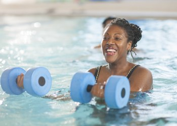 A multi-ethnic group of adults and senior adults are taking a water aerobics class in a public pool together. They are holding floating weights are are moving their arm