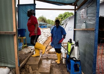 "A worker at an emergency cholera treatment centre gets her shoes disinfected in Kinshasa on January 18, 2018. The World Health Organization (WHO) on January 15 said there was a high risk of a cholera epidemic after flooding in Kinshasa, the teeming and ramshackle capital of the Democratic Republic of Congo. Beyond the capital, the latest cholera outbreak has affected 23 of the 26 provinces in the vast central African country since 2017, with ""almost 50,000 cases and around 1,000 deaths"", MSF estimates. Such figures make it the worst outbreak in DR Congo since 1994. / AFP PHOTO / JOHN WESSELS        (Photo credit should read JOHN WESSELS/AFP/Getty Images)"