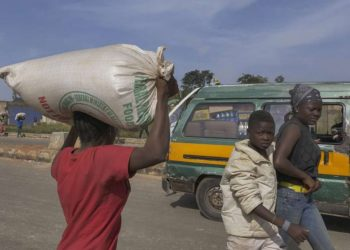 A resident carries a bag of food on her head during a mass looting of a warehouse that have COVID-19 food palliatives that were not given during lockdown to relieve people of hunger, in Jos, Nigeria, on October 24, 2020. Ifiok Ettang / AFP